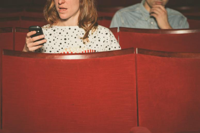 Woman using her cell phone in a theater while a young man sitting behind her watches on