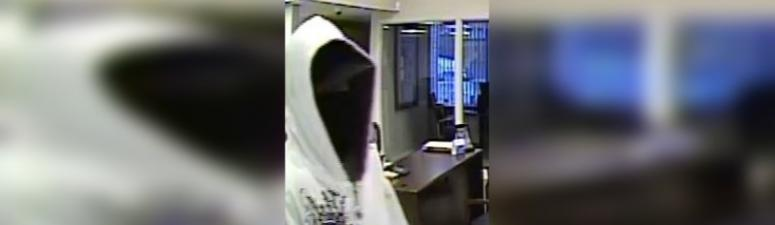 A man in his 20s wearing a white hooded sweatshirt with a design on the front and a black mask covering his face is seen in surveillance photos from Country Club Bank in Leavenworth