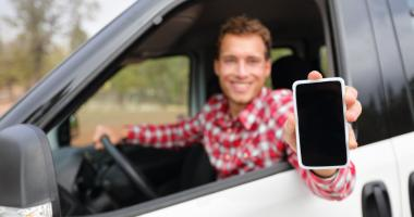 Smart phone man in car driving, showing smartphone display, smiling happy.