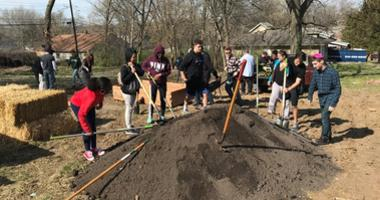 Students gather round a large pile of dirt.  Garden boxes are assembled nearby.