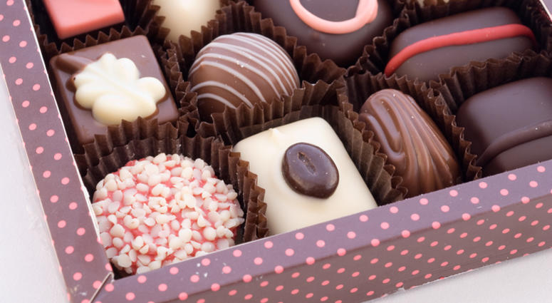 Part of box with chocolate bonbons on white background