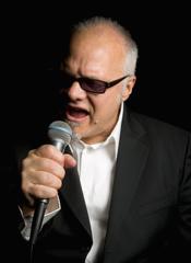 Curtis Salgado Singing Into Microphone While Wearing Sunglasses