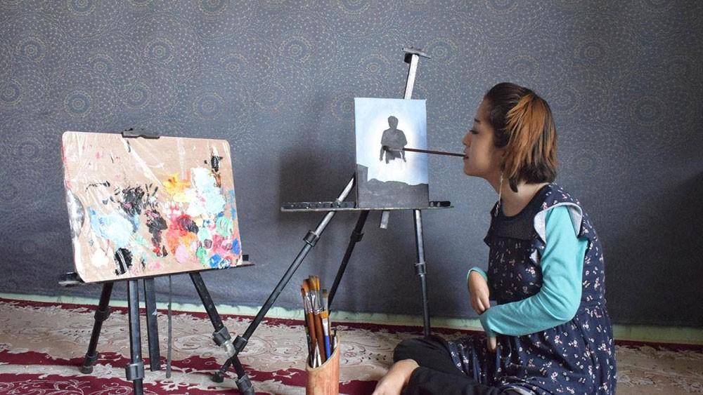 أفغانية من ذوي الاحتياجات الخاصة ترسم بفمها