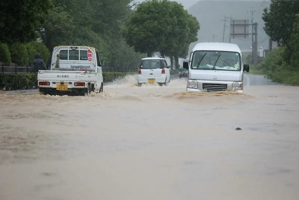 Vehicles pass through a flooded road caused by heavy rain in Yatsushiro, Kumamoto prefecture on July 4, 2020. (AFP)