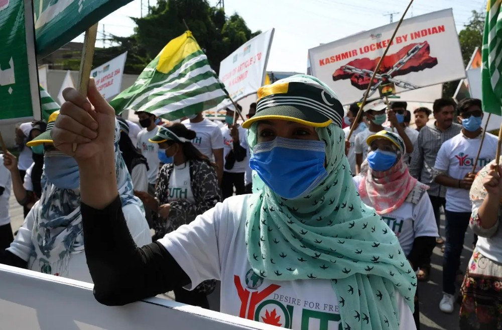 Activists of Pakistan Youth Forum Kashmir hold placards and wave Azad Kashmir flags during a rally to show their solidarity with people of Indian-administered Kashmir, in Lahore, on August 5, 2020. (AFP)