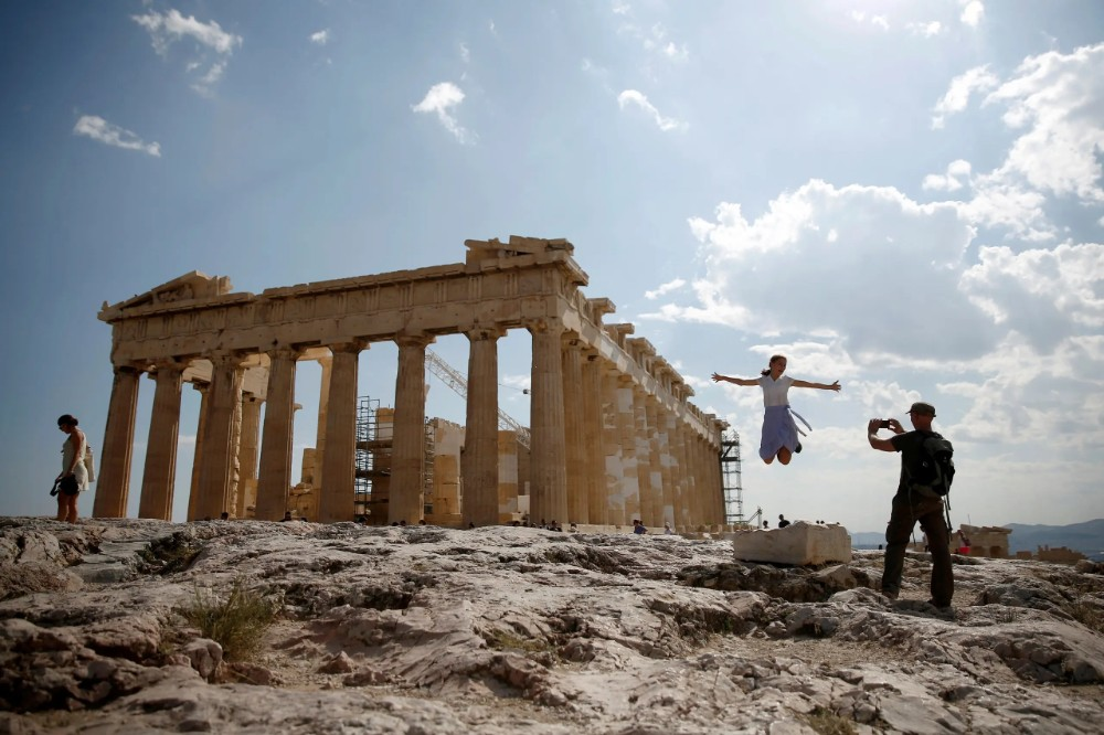 Tourists take a picture in front of the temple of the Parthenon atop the Acropolis in Athens. (Reuters)