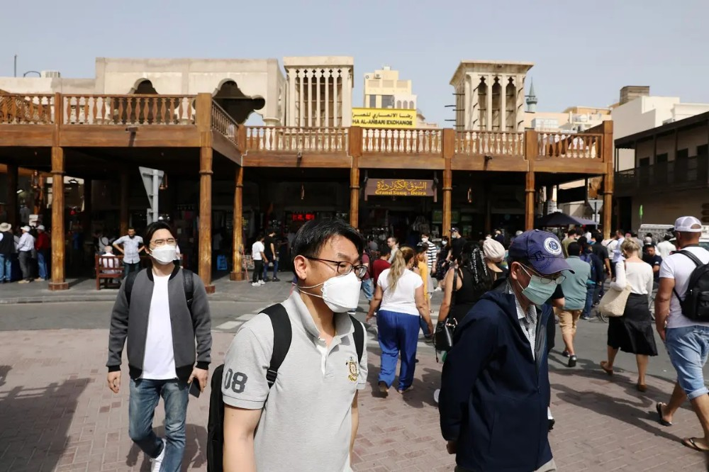 Tourists wear protective face masks as they walk at the Grand Souq in old Dubai. (Reuters)