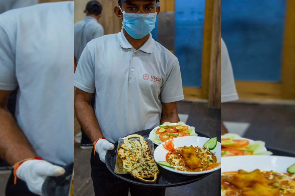 A waiter carries 'Covid Curry' and 'Mask Naan,' to serve to customers at their restaurant in Jodhpur on August 3, 2020. (AFP)