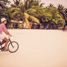 mother cycling on the beach with her toddler