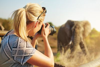 a woman taking a photo of an elephant on a safari