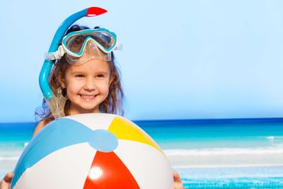 a little girl with a large beach ball