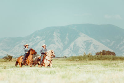 Two Cowboys Riding a Horse