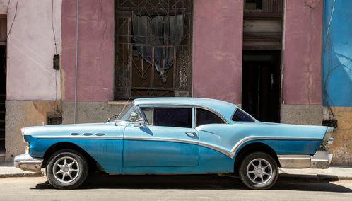 A blue classic car against a pink wall