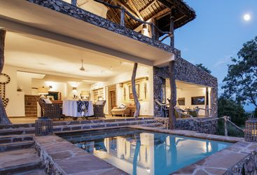 The pool area at night at Beho Beho Camp, luxury hotel in Tanzania