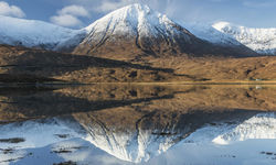 A snow capped mountain and its reflection in a lake