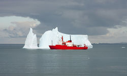 A research vessel sailing past an iceberg in Antarctica