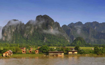 Stilted homes in front of mountains