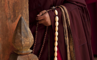 Prayer Beads Hanging from a Monk's Red Sleeve