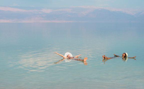 women floating in dead sea