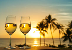 White wine glasses on a sunset beach