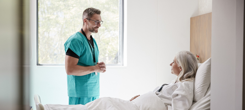 Doctor and female patient speaking in a hospital room
