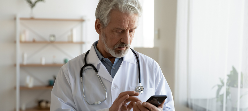 Doctor with a mobile phone in his hand.