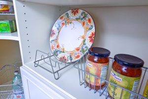 Organized-Living-nickle-lid-organizer-and-simple-basket-in-pantry-holding-plates-and-jars