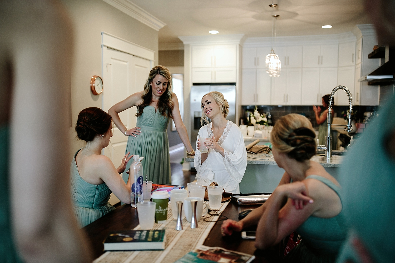 bridesmaid in dresses talking to bride in bridal robe