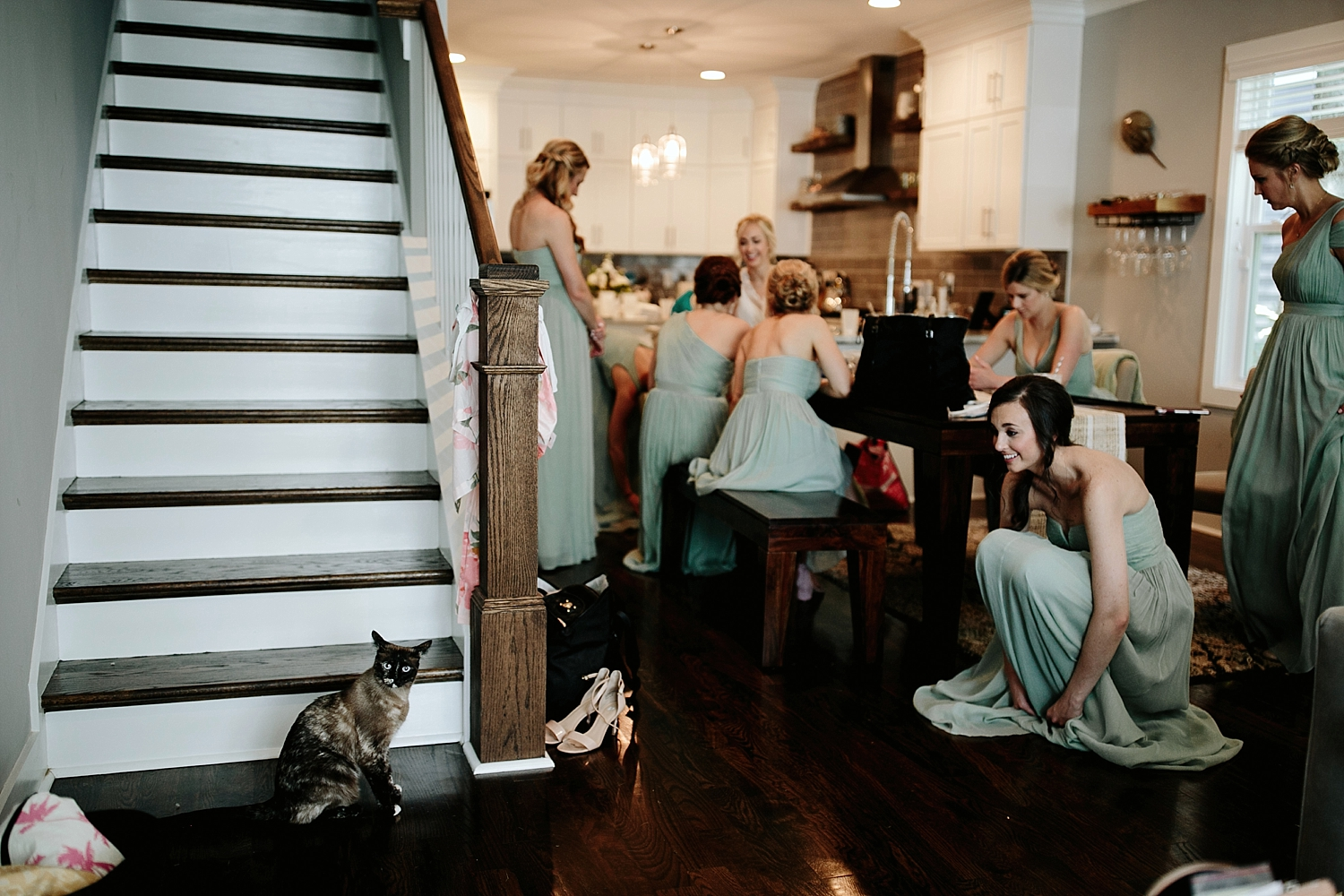 bridesmaid smiling at cat on staircase
