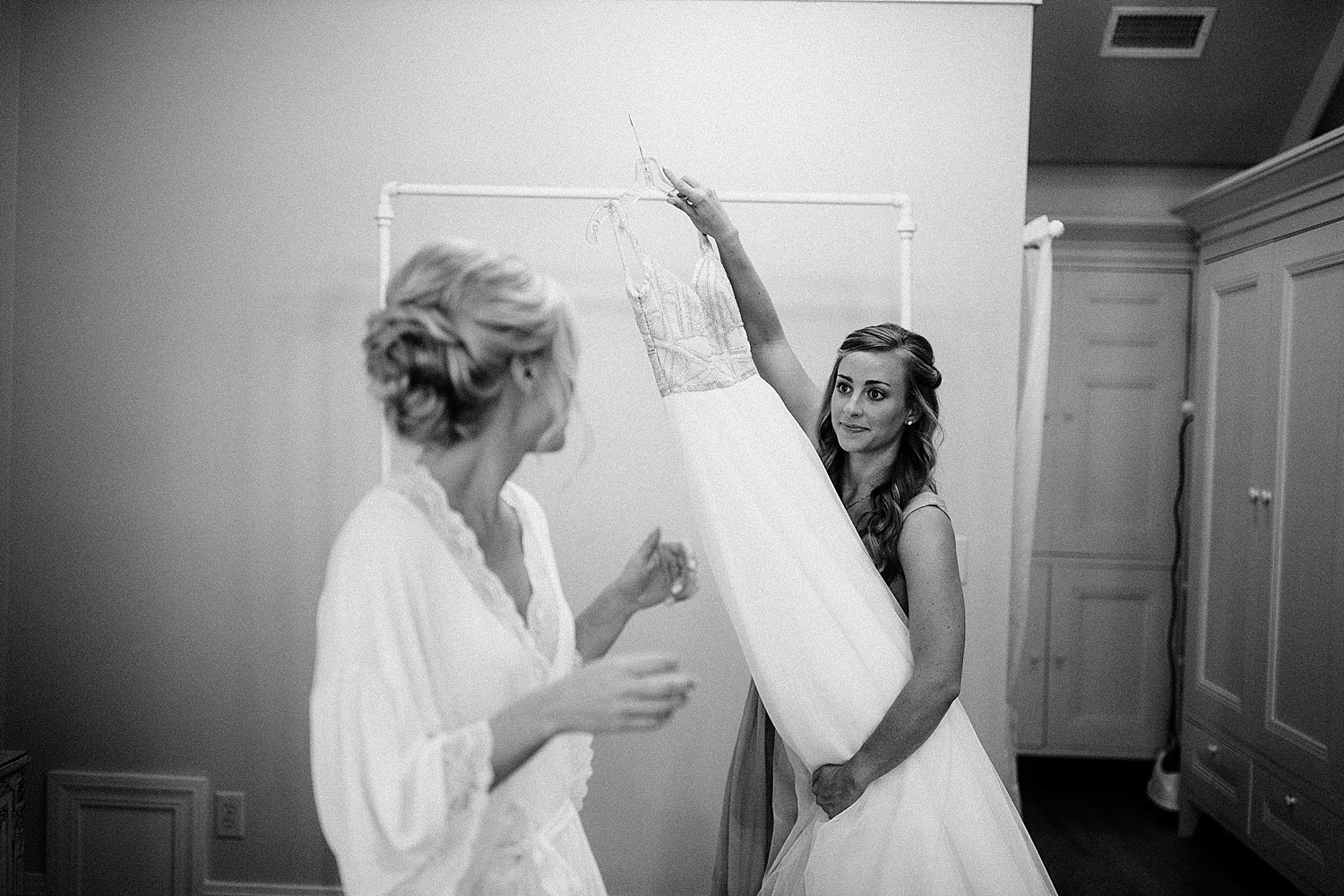 bridesmaid pulling dress off of hanger for bride