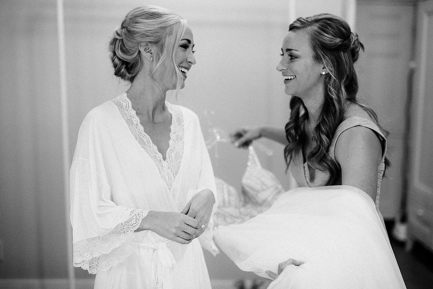 bride and bridesmaid smiling while holding bridal dress