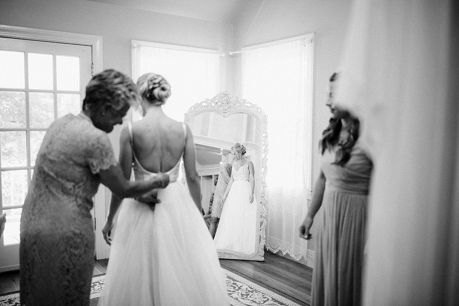 mother of the bride and bridesmaid helping button brides dress