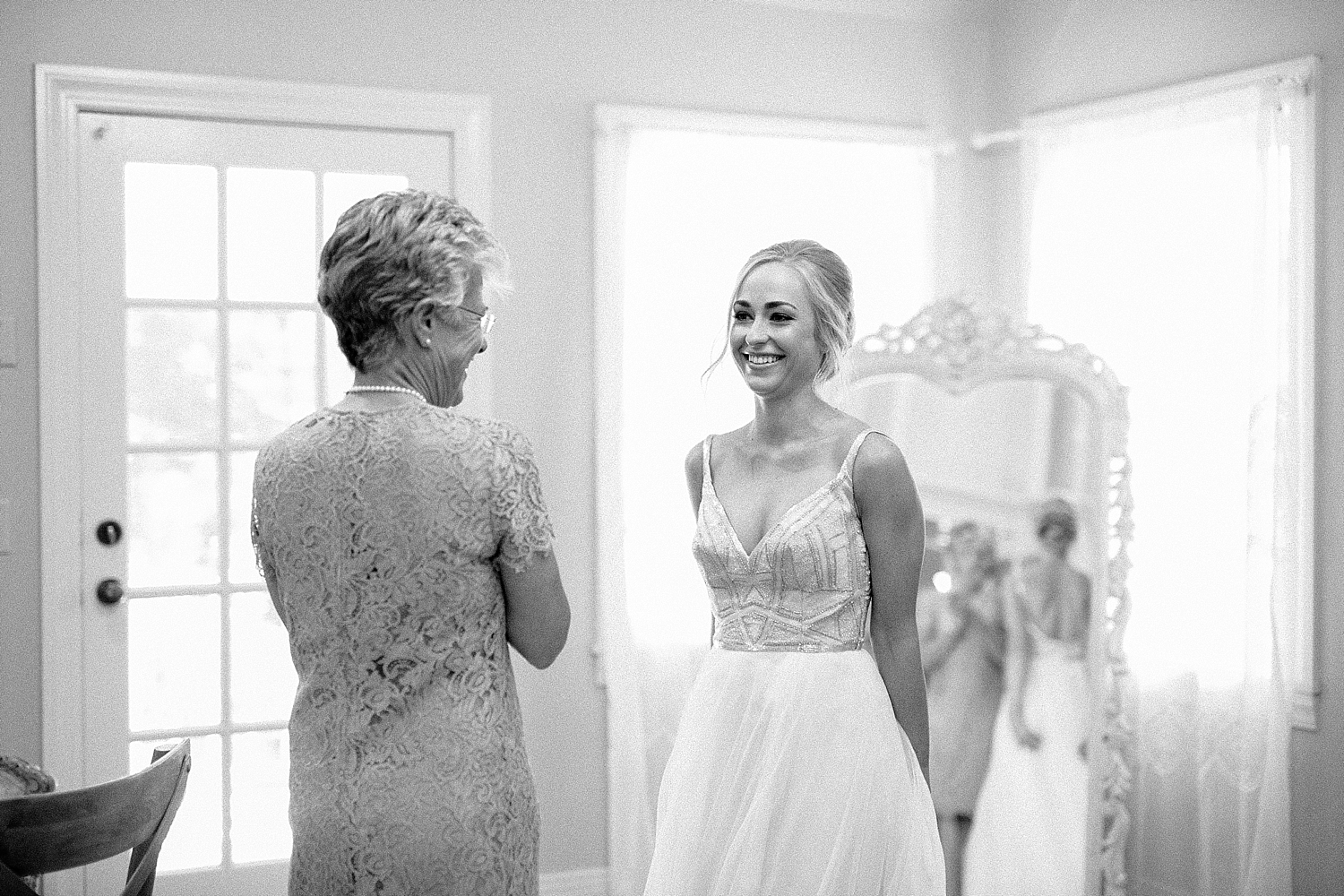 mother of the bride smiling at bride in her wedding dress