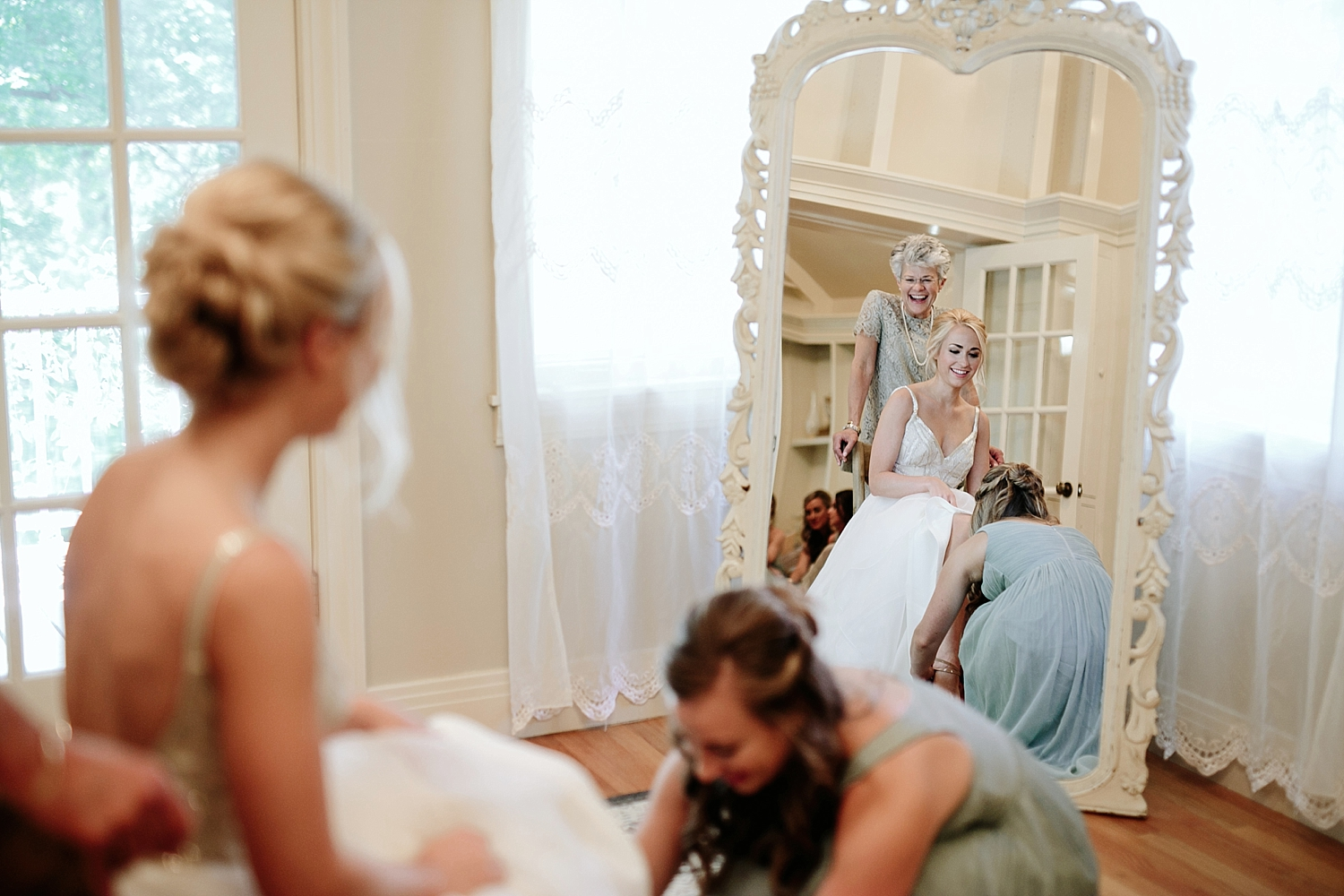 bridesmaid helping bride put sandals on
