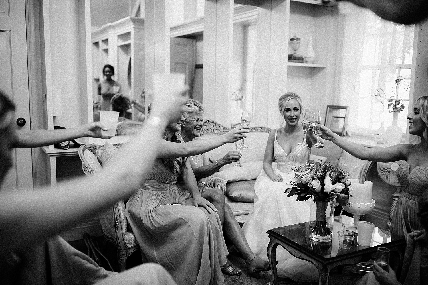bride and bridesmaid clinking champagne glasses