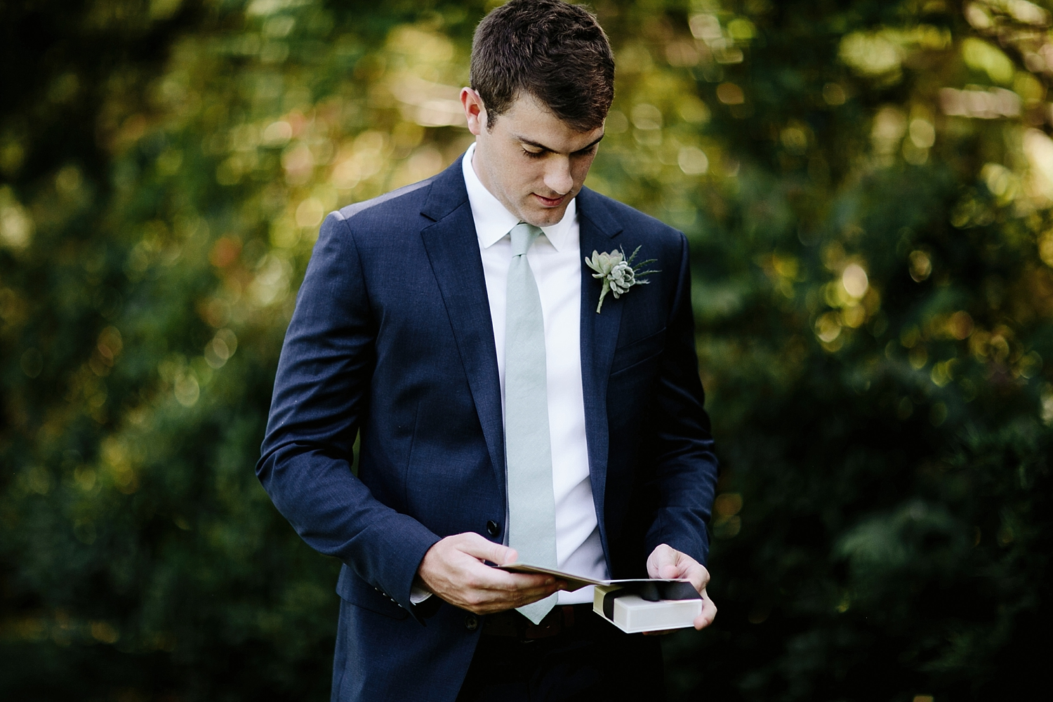 groom looking at brides gift to him
