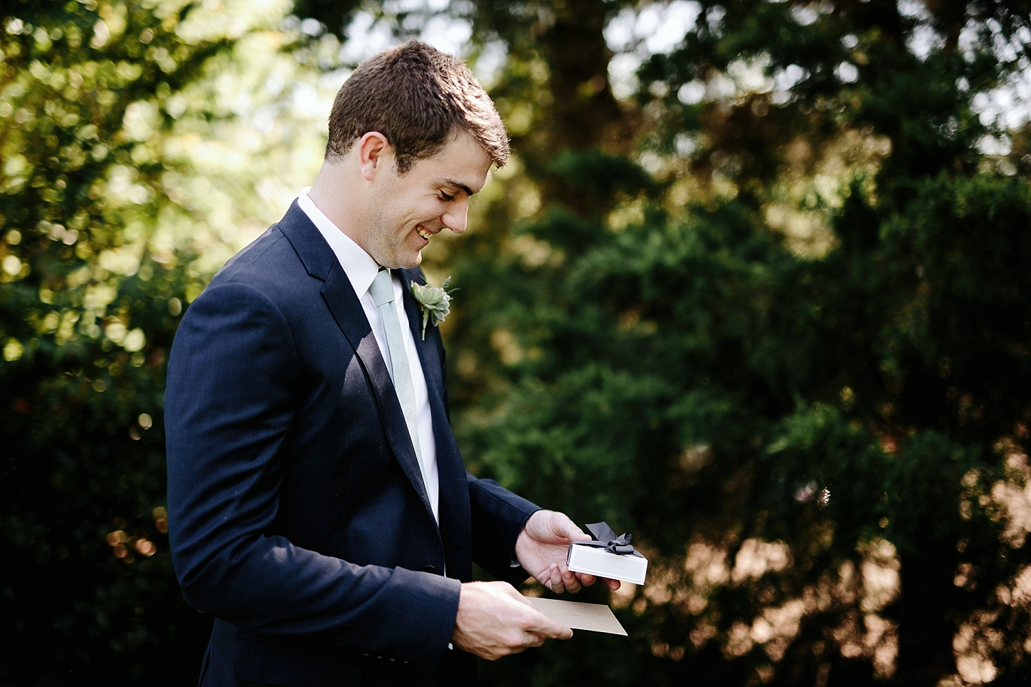 groom laughing at brides gift