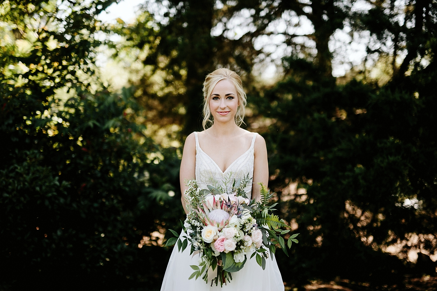 bride holding bouquet of flowers in the woods