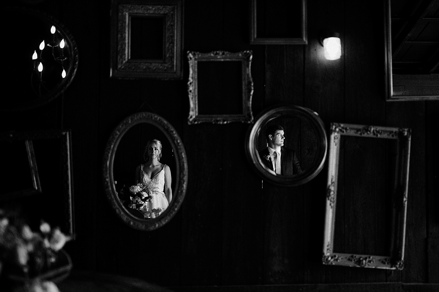 bride and groom staring into separate hanging mirrors
