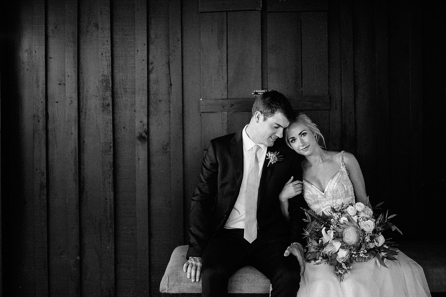 bride holding grooms arm while sitting on bench