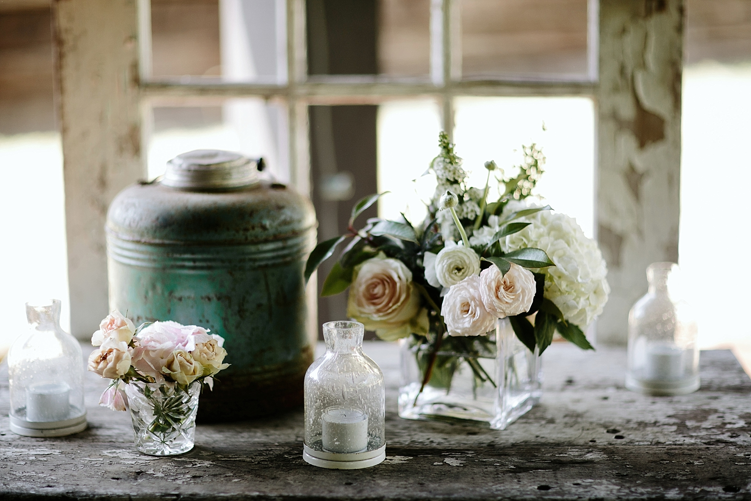 white flowers in small vases with candles