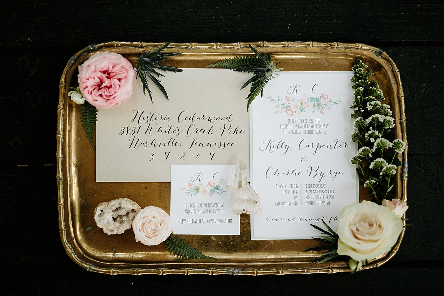 wedding invitation sitting on golden platter surrounded by flowers