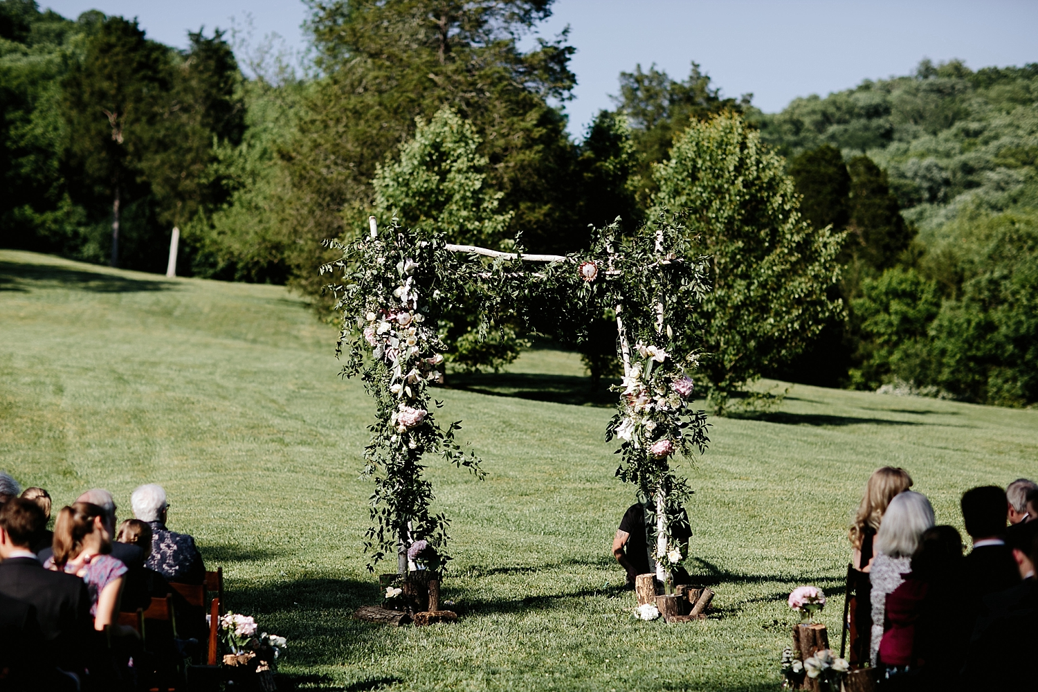 guests sitting in ceremony chair with floral arbor at the center