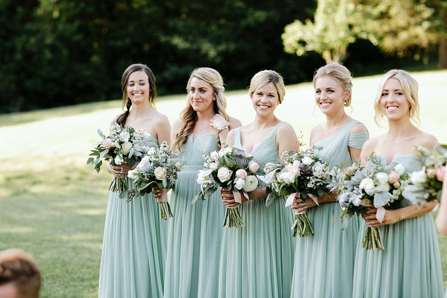 bridesmaids with bouquets standing during ceremony