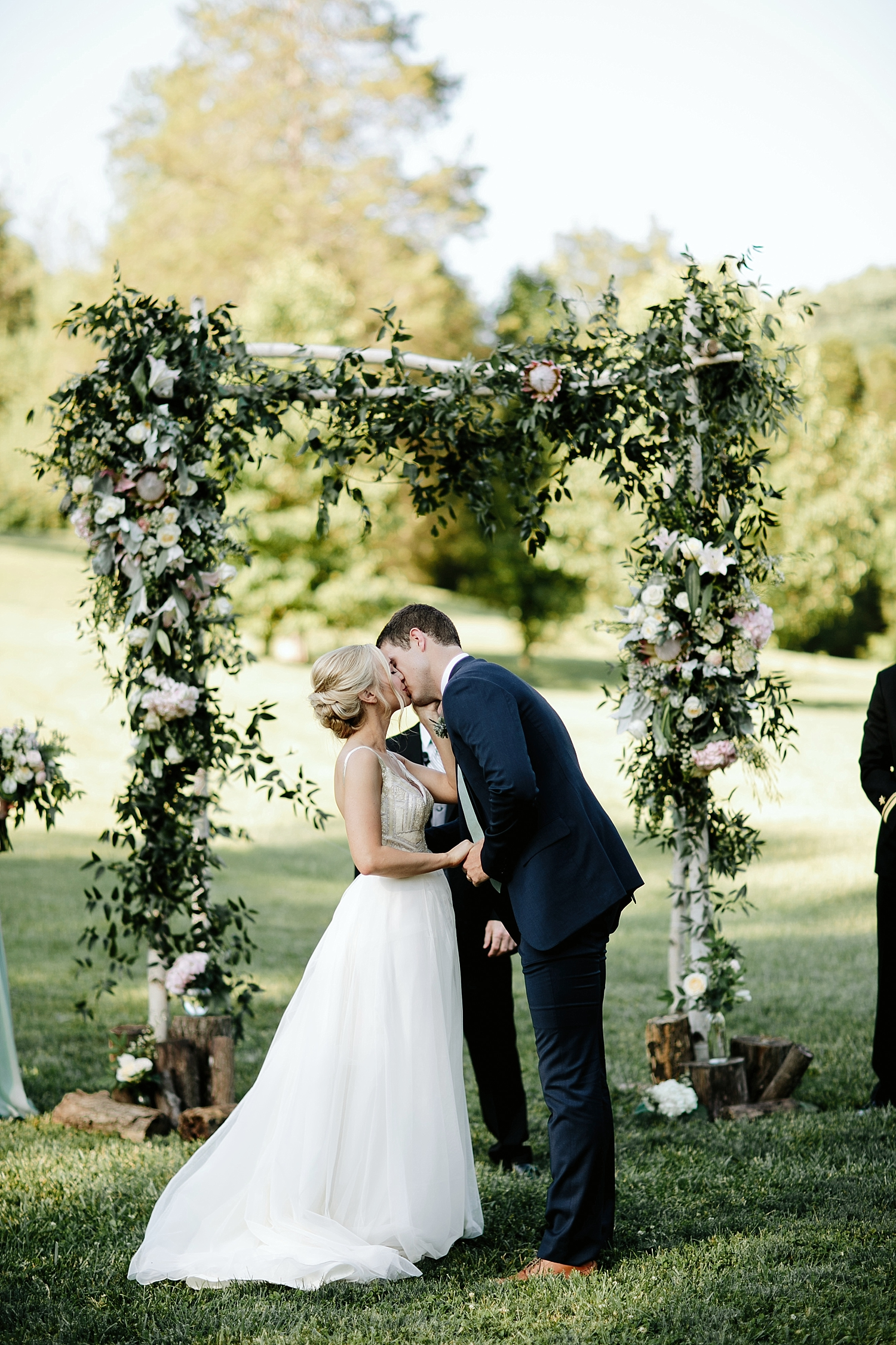 bride and groom first kiss in front of floral arbor