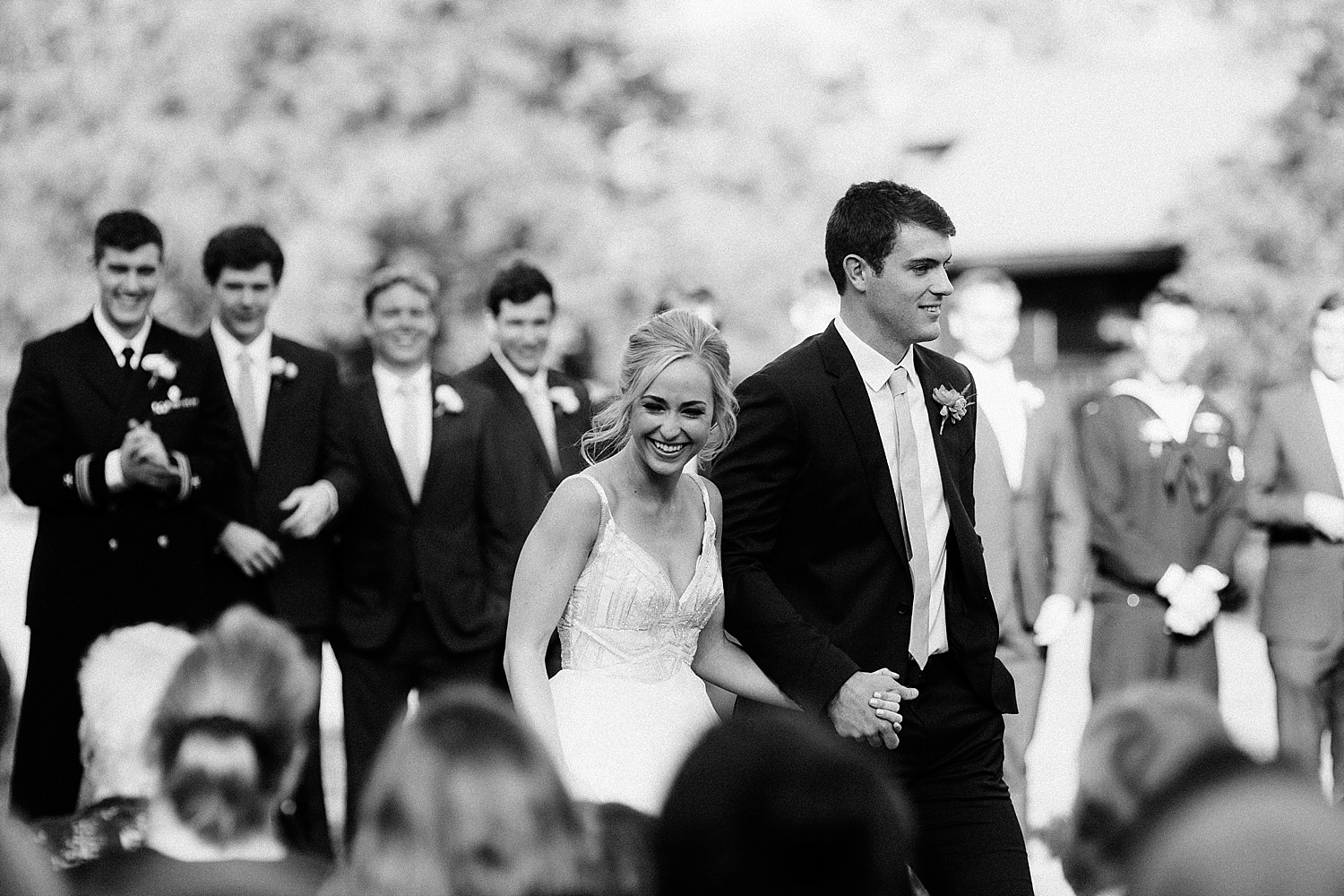 bride smiling at guests while walking down the aisle with groom