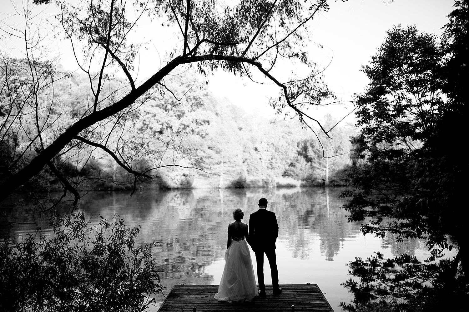 bride and groom standing on boating dock at lake