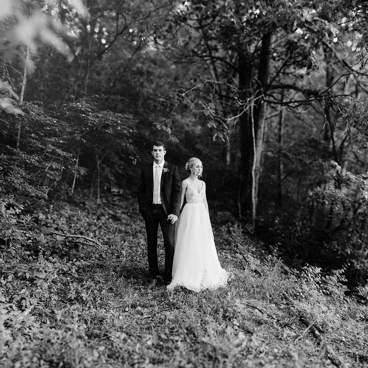 bride and groom holding hands in the center of the woods