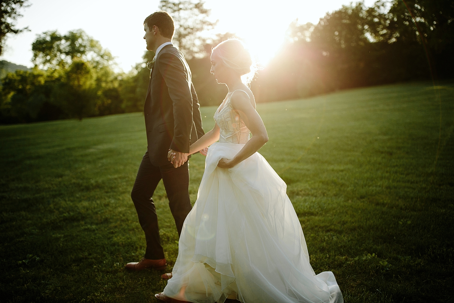 bride and groom holding hands while sun sets