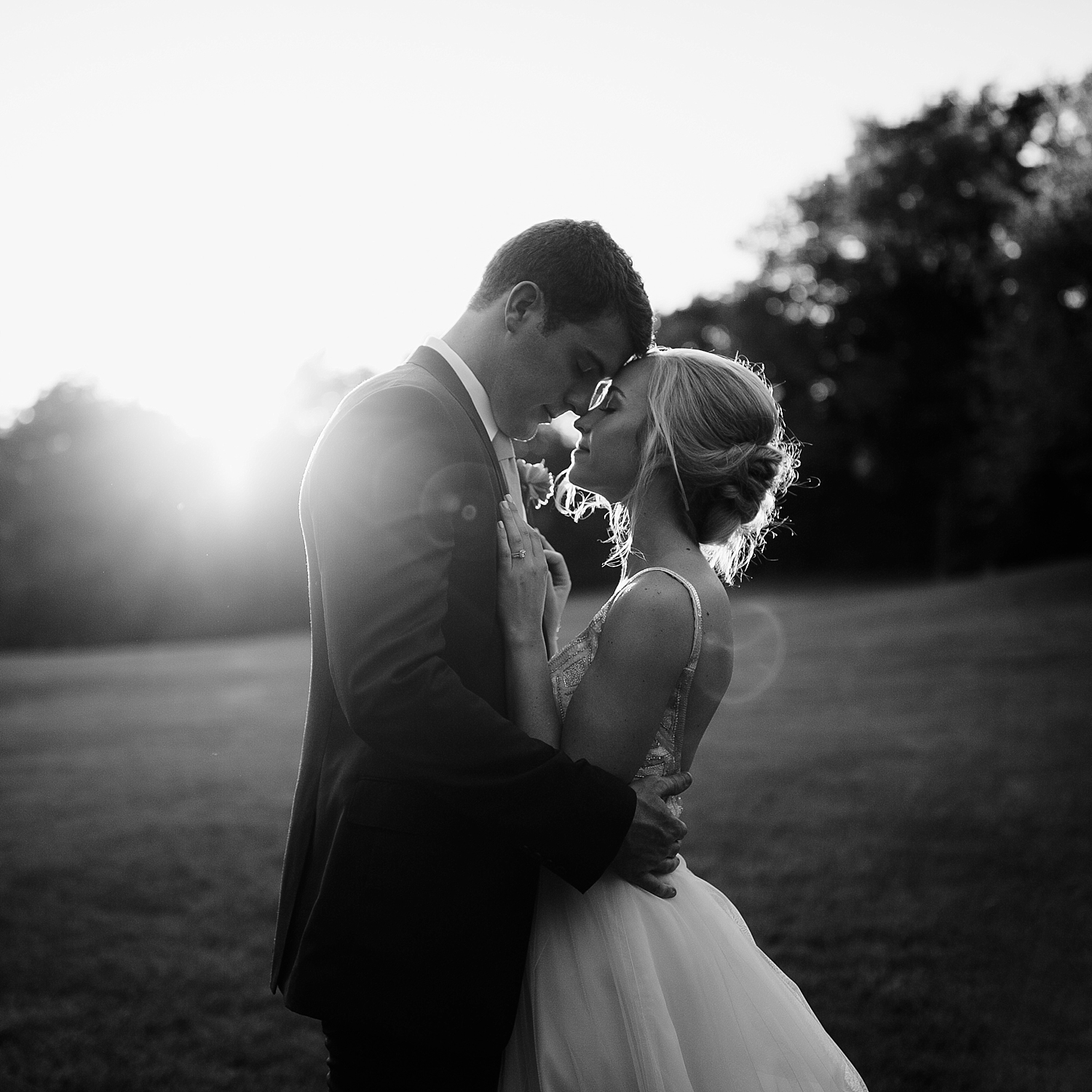 bride and groom touching foreheads with sun setting behind them